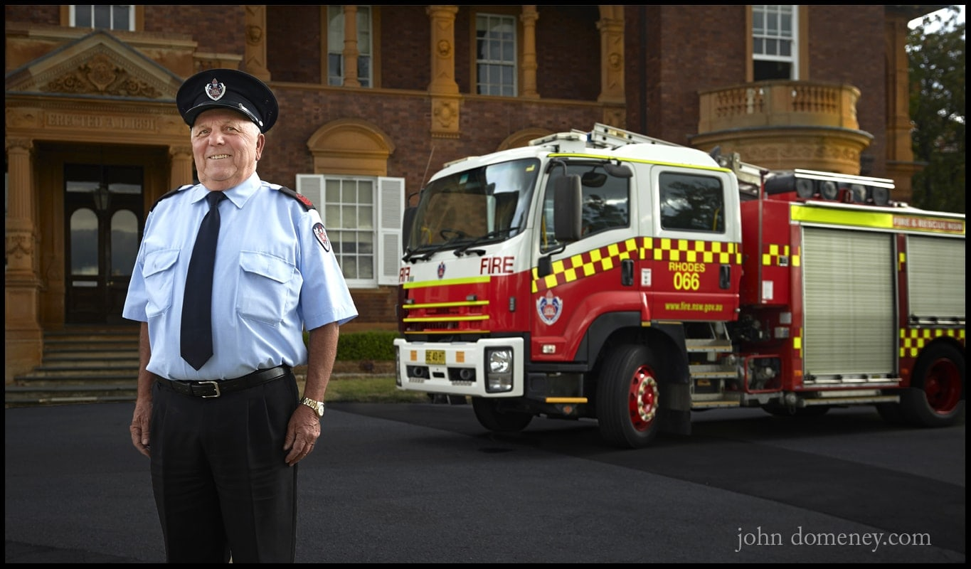 Retiring Firefighter stands in front of his Fire truck and a historic building at sunset.